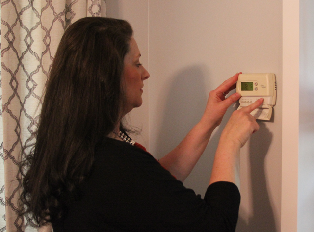 A woman operating her home's HVAC system with a wall-mounted thermostat