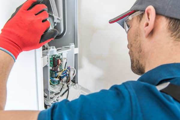 An over-the-shoulder view of a repair technician fixing the electrical components of a furnace