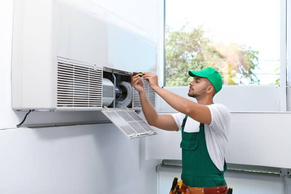A technician installing the indoor unit of an HVAC system